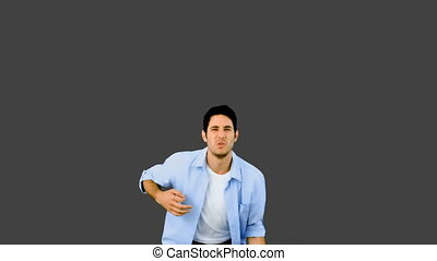 Man playing air guitar on grey background in slow motion