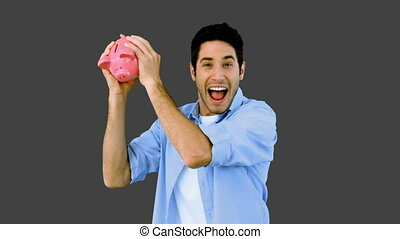 Man shaking piggy bank excitedly on grey background in slow...
