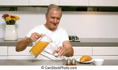 Retired man pouring orange juice for breakfast in the...