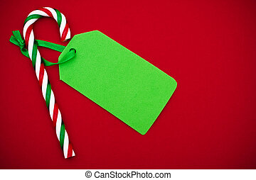Sweet Gift - Candy cane with blank green gift tag on red...