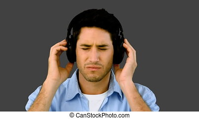 Man listening to music with headphones on grey background in...