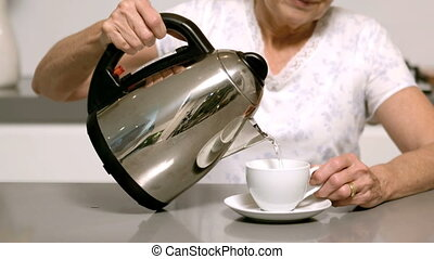 Woman pouring boiling water from kettle into cup in slow...