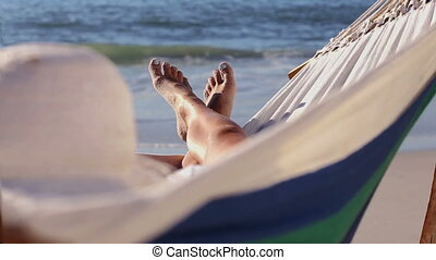 Woman relaxing on the beach in a ha