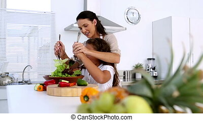 Mother and daughter tossing salad together at home in...