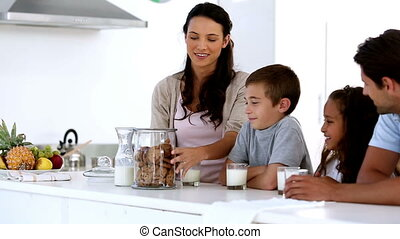 Mother giving cookies to her family at home in kitchen