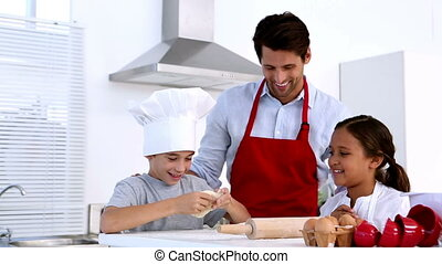 Father watching son stretch pastry with sister at home in...