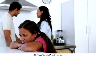 Little girl feeling sad as parents fight at home in kitchen