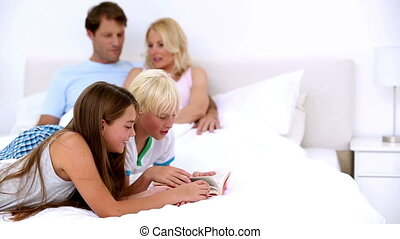Parents chatting as children are reading at home in bedroom