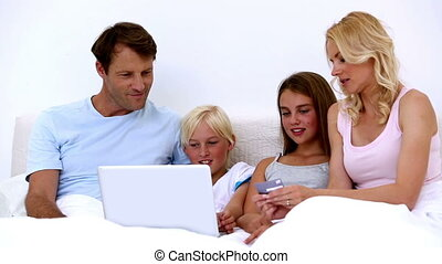 Cute family using laptop to shop online together at home in...