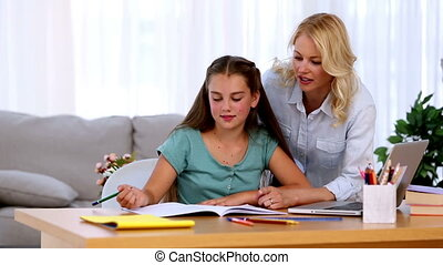 Mother helping her daughter with homework and smiling at...