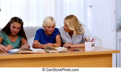 Parents helping their children with their homework at a desk
