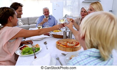 Family toasting at dinner table at home in kitchen