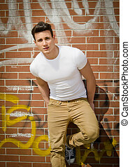 Handsome young man on city brick wall - Attractive young man...