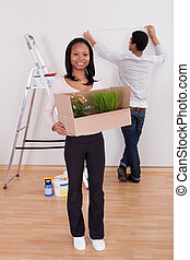 Couple Carrying Boxes In House - Portrait Of Young Couple...