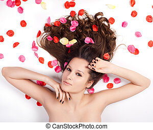 beautiful woman with curly hair in the petals of roses