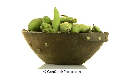 Green beans pod on wooden bowl rotate on white background.