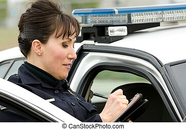 Traffic stop - a female police officer writes a ticket while...