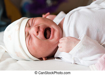 Newborn baby crying on the bed, selective focus