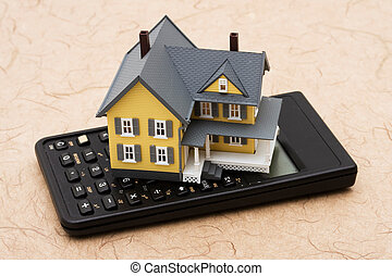 Mortgage Calculator - Model house sitting on calculator,...