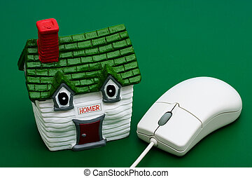 Online Real Estate - House sitting with computer mouse with...