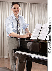 Composer - A young music composer standing near grand piano