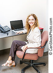 Smiling woman sitting at office desk - Happy businesswoman...