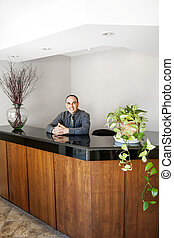 Smiling man standing at office reception