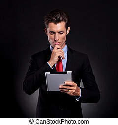 business man with pad, thinking - portrait of a young...