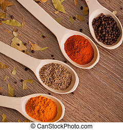 spices on spoons - aromatic powder spices on spoons in...