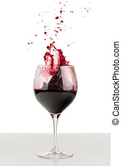 Splash of red wine in a wineglass. - Splash of red wine in...