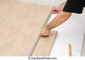 carpenter worker installing laminate board during flooring work