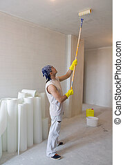 worker painting ceiling with painting roller - Young man -...