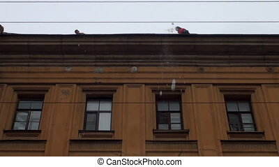 Workers clean the roof from snow
