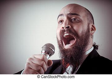 funny elegant singer bearded on vignetting background