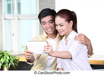 Asian couple using tablet computer