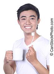 Asian guy brushing teeth, isolated on white