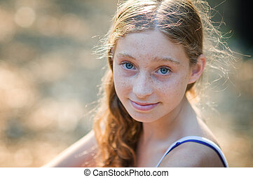closeup of a pretty teenage girl with blue eyes and freckels
