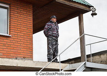 Security guard - A security guard in camouflage at the post