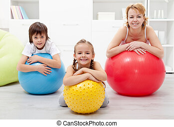Happy healthy family relaxing and resting during gymnastic exercise