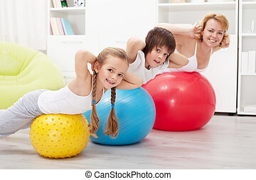 Happy healthy family exercising at home with large gymnastic...