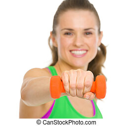 Closeup on happy fitness young woman making exercise with dumbbells