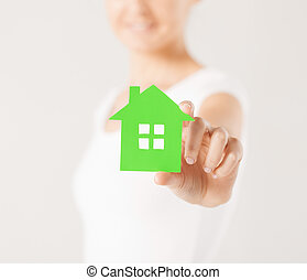 woman hands holding green house - closeup picture of woman...
