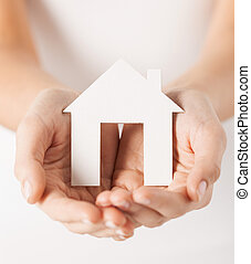 woman hands holding paper house - closeup picture of woman...