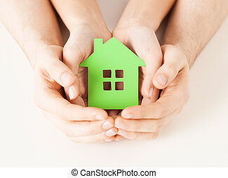 couple hands holding green house - closeup picture of woman...