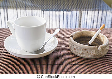 Cup of coffee and cigarette ashtray composition