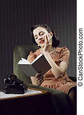 Young woman daydreaming while reading a textbook