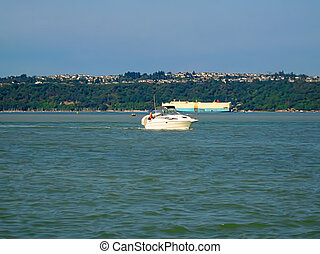 Motorboat And Container Ship - A photograph of a small motor...