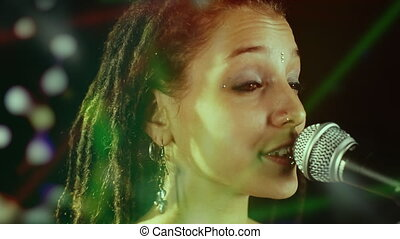 beautiful singer with dreadlocks, with overlayed concert lights