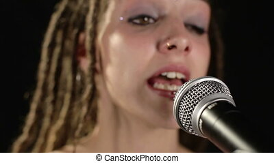 beautiful singer with dreadlocks singing into microphone