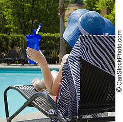 Girl with water bottle by the pool - Girl in blue hat with...